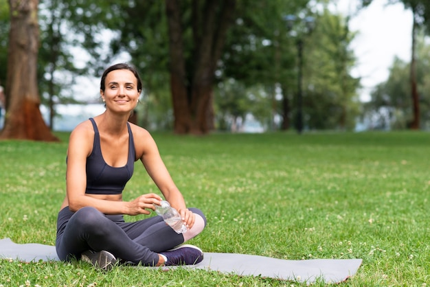 Tiro completo mulher sentada no tapete de ioga