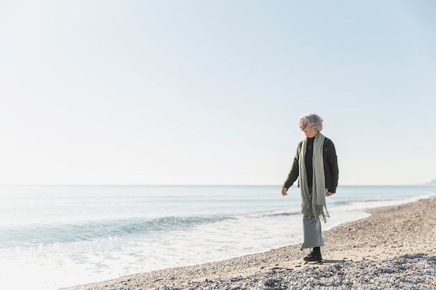 Tiro completo velha andando à beira-mar