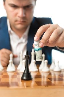 Tiro conceitual de poder do dinheiro. homem fazendo movimento de xadrez com notas de dólar