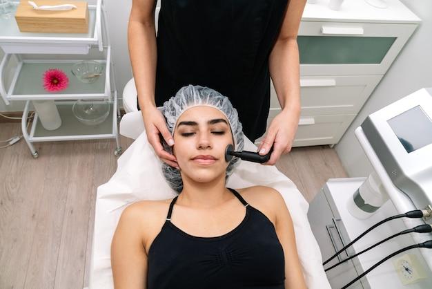 Tiro curto da esteticista dando tratamento de radiofrequência no rosto de uma mulher que rejuvenesce e estimula a função celular saudável