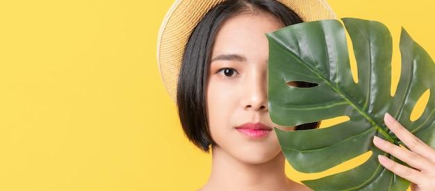 Tiro da beleza da mulher asiática que guarda as folhas verdes para tocar na cara na laranja.
