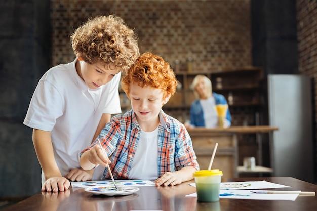 Tiro da cintura para cima de duas crianças adoráveis de cabelos encaracolados em pé perto uma da outra e pintando em uma mesa, enquanto sua avó atenta os observa ao fundo.