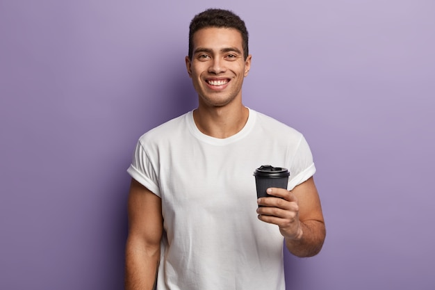 Tiro da cintura para cima de um cara bonito sorridente e alegre segurando um café para viagem de papel, aproveitando o tempo livre com um amigo, bebe uma bebida aromática, usa uma camiseta branca simulada, modelos contra a parede roxa