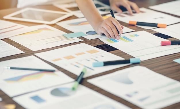 Tiro da mão do homem que trabalha com o documento gráfico ou gráfico no escritório
