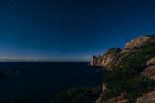 Tiro da noite de céu azul escuro estrelado, montanhas e mar na aldeia de novy svet na crimeia