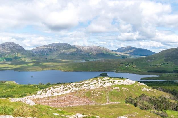 Tiro da paisagem das montanhas e do lago contra o céu nublado, connemara, irlanda.