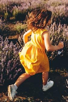 Tiro da vista traseira de uma menina correndo em um campo de flores. menina vestida de vestido amarelo, brincar ao ar livre.