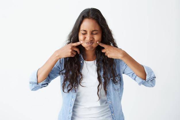 Tiro de afro-americana morena vestida casualmente com os olhos fechados, fazendo careta soprando as bochechas, tocando-os com os dedos, tendo expressão de prazer.