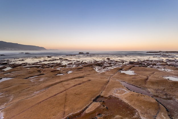 Tiro de alto ângulo bonito da terra perto do corpo da água do oceano à noite