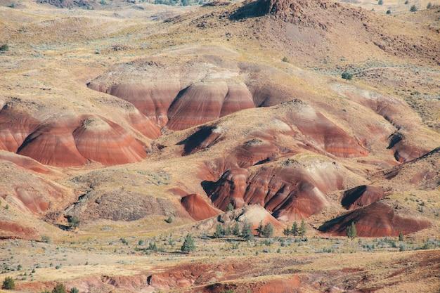 Tiro de alto ângulo das colinas vermelhas arenosas em uma área deserta sob o céu brilhante