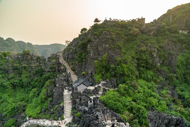 Tiro de alto ângulo de altas montanhas rochosas, com árvores verdes e caminhos curvos sob o céu claro