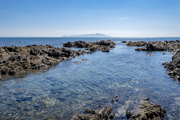 Tiro de alto ângulo de formações rochosas na água da baía de pukerua na nova zelândia