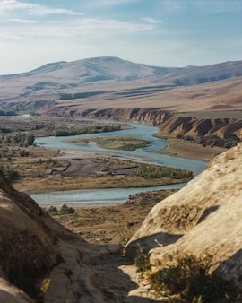 Tiro de alto ângulo de um rio cheio de curvas, rodeado por altas montanhas sob o céu nublado