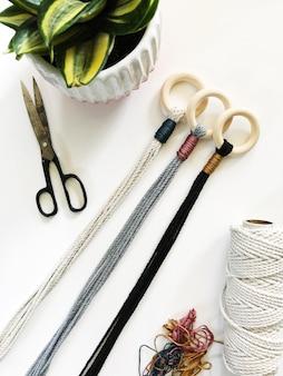 Tiro de alto ângulo de uma mesa branca com tesoura, uma planta em uma panela branca e fios coloridos