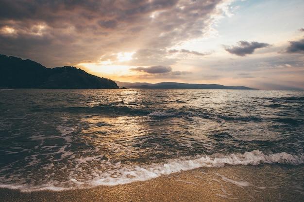 Tiro de ampla paisagem de um mar perto de montanhas ao longe sob um céu durante o pôr do sol
