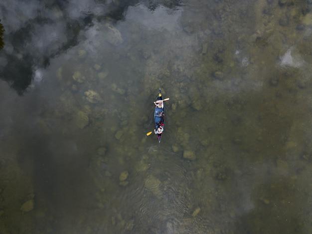 Tiro de ângulo alto de duas pessoas em um barco a remo em um lago