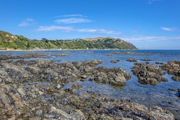 Tiro de ângulo alto de formações rochosas na água da baía de pukerua na nova zelândia