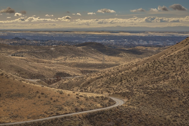 Tiro de ângulo alto de uma estrada curvilínea no meio de montanhas com edifícios da cidade à distância