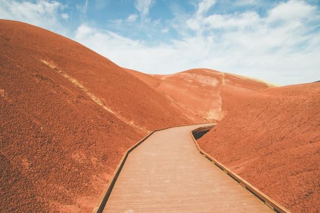 Tiro de ângulo alto de uma estrada de madeira sintética nas colinas de areia vermelhas sob o céu brilhante
