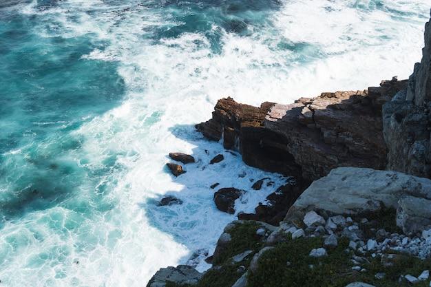 Tiro de ângulo alto de uma formação rochosa perto do corpo de água turquesa