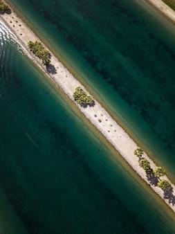 Tiro de ângulo alto de uma linha de areia estreita com árvores verdes no meio do mar