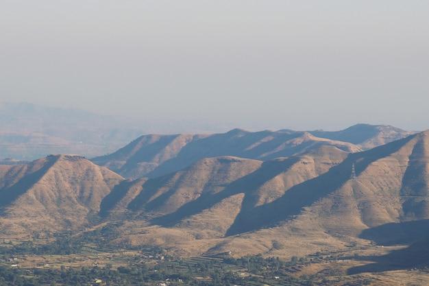 Tiro de ângulo alto do cenário de colinas, refletindo os raios do sol sob o céu claro