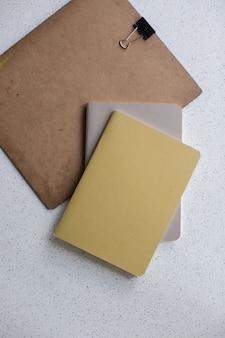 Tiro de ângulo alto vertical de cadernos marrons e cinza e uma placa em uma superfície branca