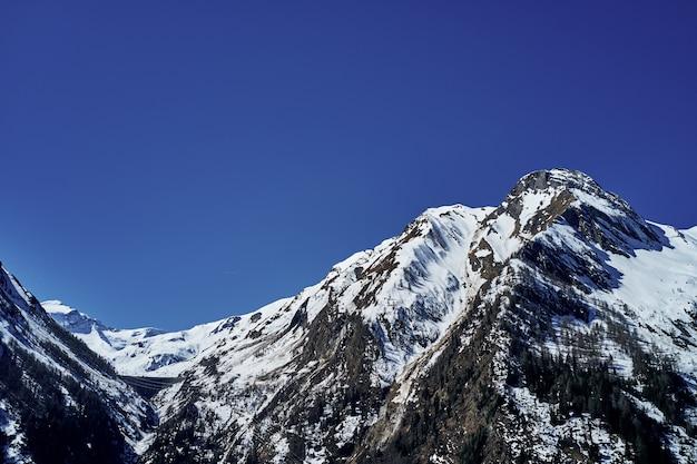 Tiro de ângulo baixo bonito de uma montanha com neve cobrindo o pico e o céu ao fundo