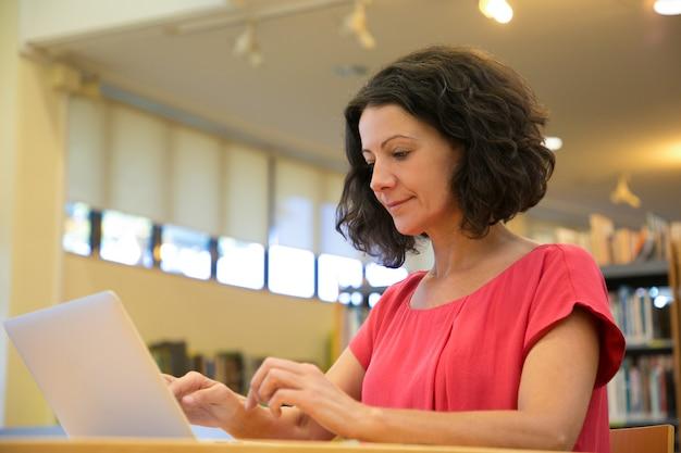 Tiro de ângulo baixo da mulher focada digitando no laptop