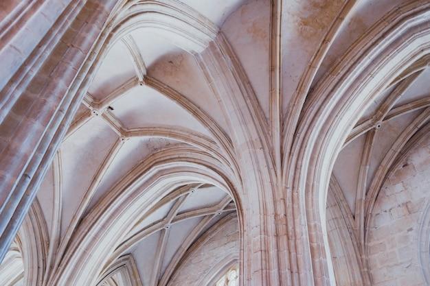 Tiro de ângulo baixo das colunas brancas e o teto de um prédio antigo