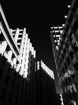 Tiro de ângulo baixo de edifícios altos de pedra perto um do outro, filmado em preto e branco
