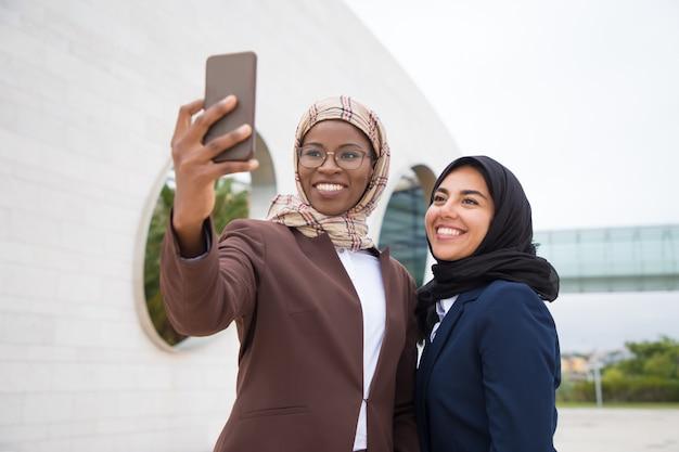 Tiro de ângulo baixo de empresárias muçulmanas sorridentes tomando selfie