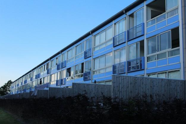 Tiro de ângulo baixo de um antigo prédio azul cercado por grama verde, sob o céu azul