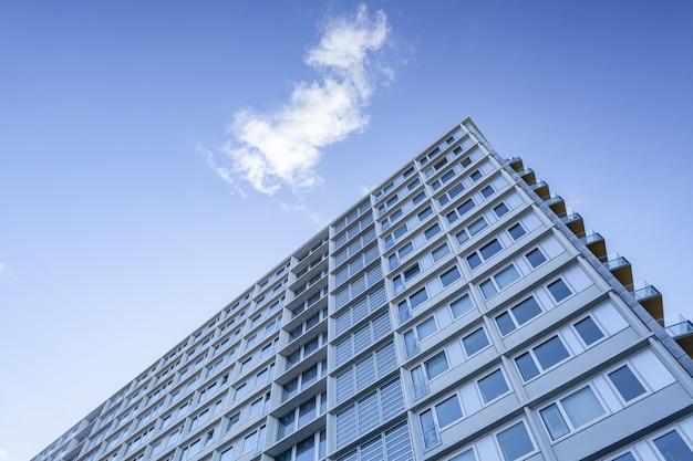 Tiro de ângulo baixo de um grande edifício sob uma nuvem no lindo céu azul
