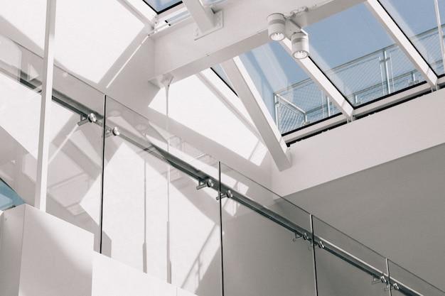 Tiro de ângulo baixo de um interior de edifício moderno, com paredes brancas tocando o céu