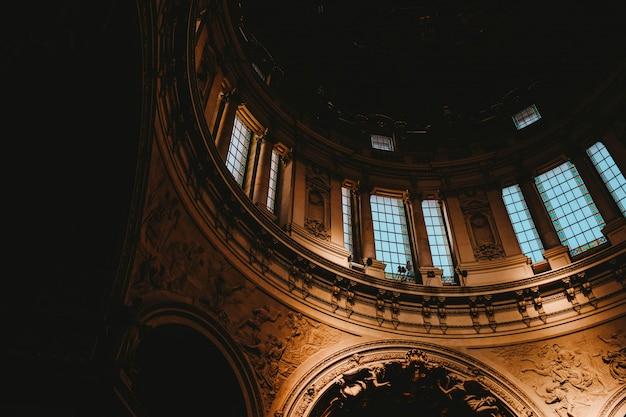 Tiro de ângulo baixo de um interior de igreja com arte medieval hipnotizante