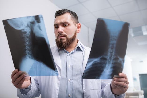 Tiro de ângulo baixo de um médico barbudo olhando focado, examinando exames de raio-x de um paciente
