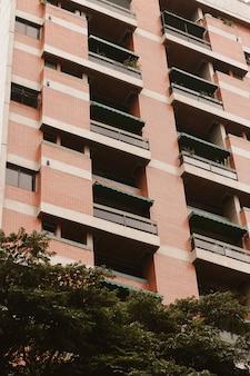 Tiro de ângulo baixo de um prédio alto com vegetação abaixo