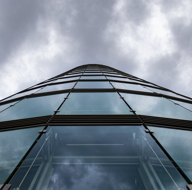 Tiro de ângulo baixo de um prédio alto em uma fachada de vidro sob as nuvens de tempestade