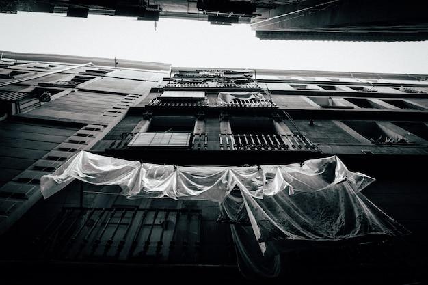 Tiro de ângulo baixo de um prédio de apartamentos com varandas em preto e branco