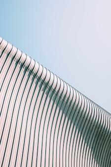 Tiro de ângulo baixo de um telhado de prédio cinza e branco com texturas interessantes sob o céu azul