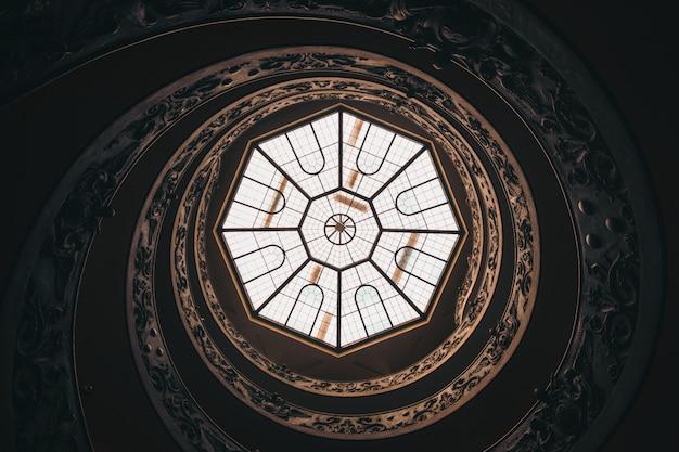 Tiro de ângulo baixo de um teto redondo com uma janela em um museu no vaticano durante o dia