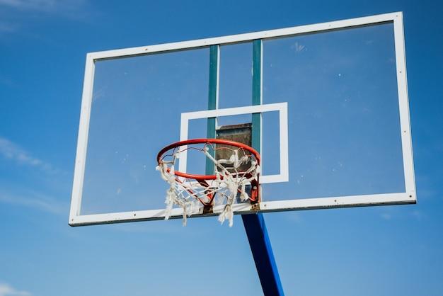Tiro de ângulo baixo de uma cesta de basquete sob um céu azul