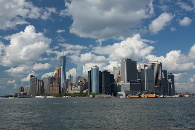 Tiro de ângulo baixo de uma cidade industrial com arranha-céus à beira de um mar e sob o céu nublado