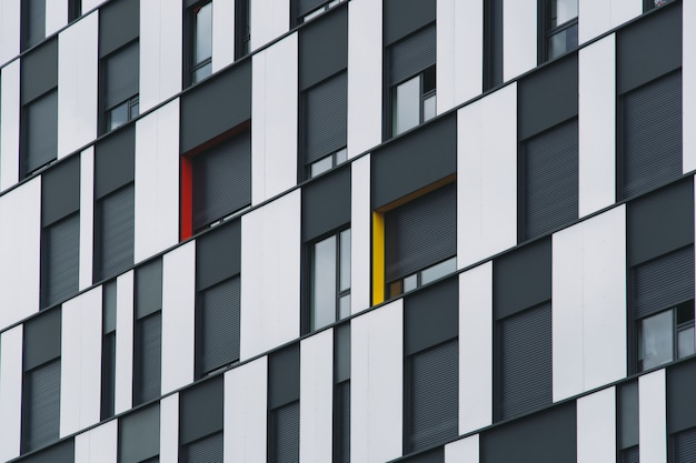 Tiro de ângulo baixo de uma fachada em preto e vidro de um edifício moderno