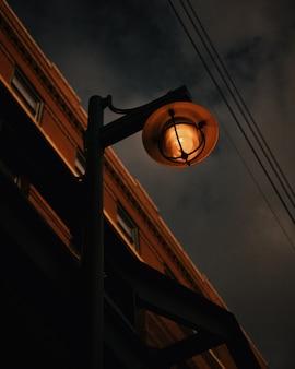 Tiro de ângulo baixo de uma lâmpada de rua enferrujada em um céu cinza