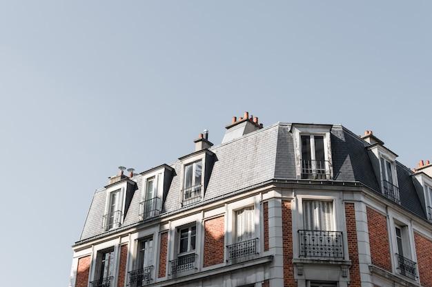 Tiro de ângulo baixo do telhado de um belo edifício com varandas em paris