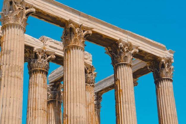 Tiro de ângulo baixo dos antigos pilares de pedra grega, com um céu azul claro