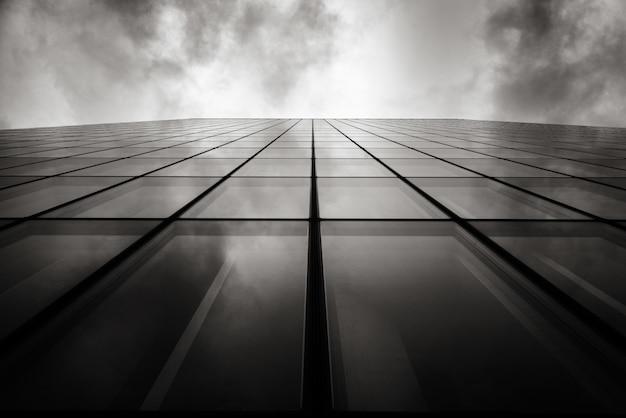 Tiro de ângulo baixo em escala de cinza de um arranha-céu de uma parede com janelas de vidro sob o céu nublado