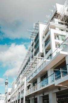Tiro de ângulo baixo vertical de um edifício moderno branco tocando o céu nublado